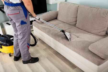 Photo pour Rear View Of Young Male Worker Cleaning Sofa With Vacuum Cleaner - image libre de droit