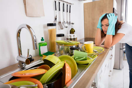 Photo pour Tired Young Woman Standing In The Kitchen Looking At The Utensil In The Sink - image libre de droit