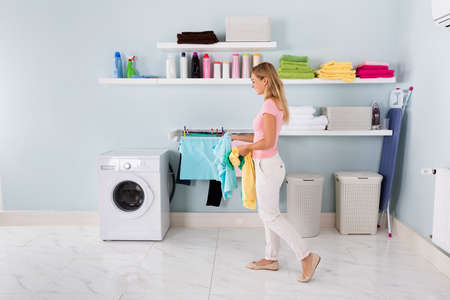 Happy Woman Washing Stained Clothes In Washing Machine In Utility Roomの写真素材