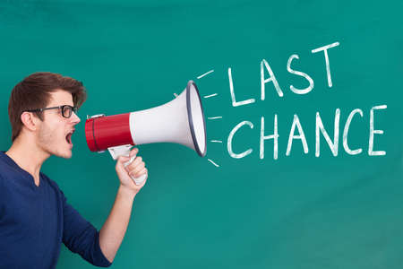 Photo pour Young Man Shouting Last Chance On Megaphone At Blackboard - image libre de droit