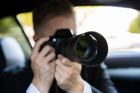 Photo pour Private Detective Sitting Inside Car Doing Surveillance Work Photographing With Camera - image libre de droit