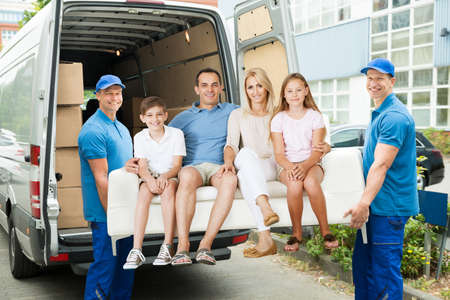 Photo for Two Male Happy Furniture Movers Carrying Family On Sofa Out Of Truck Outside The House. - Royalty Free Image