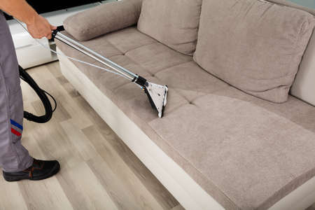Photo pour Young Male Worker Cleaning Sofa With Vacuum Cleaner - image libre de droit