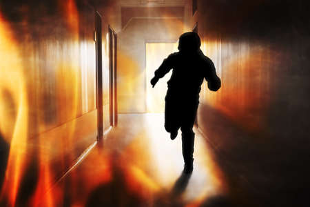 Photo pour Silhouette Of Person Running Out Of Fire Escape On Corridor Of Building - image libre de droit