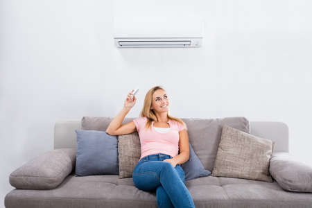 Photo pour Young Happy Woman Sitting On Couch Operating Air Conditioner With Remote Control At Home - image libre de droit