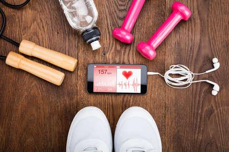 Foto de Exercise Equipment With Mobilephone Showing Health Application On Wooden Floor - Imagen libre de derechos