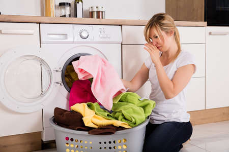 Photo pour Young Woman Looking At Smelly Clothes Out Of Washing Machine In Kitchen - image libre de droit