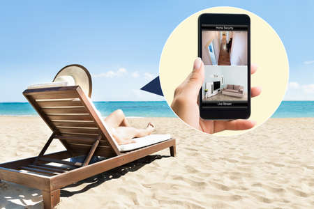 Photo pour Woman Relaxing On Lounge Chair At Beach Looking At Security System On Mobile Phone - image libre de droit