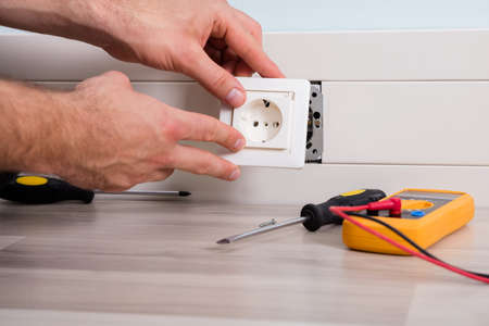 Photo pour Close-up Of Person's Hand Installing Socket On Wall At Home - image libre de droit