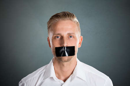 Photo pour Young Man With Black Duct Tape Over His Mouth Against Grey Background - image libre de droit