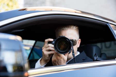 Photo pour Man Sitting Inside Car Photographing With SLR Camera - image libre de droit