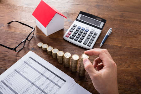 Photo pour High Angle View Of A Person Stacking Coins Near House On Wooden Desk. Property Tax Concept - image libre de droit
