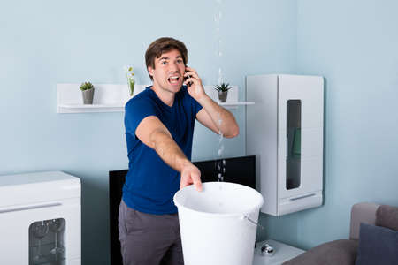 Photo pour Worried Man Calling Plumber While Leakage Water Falling Into Bucket At Home - image libre de droit