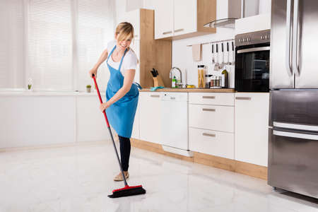 Foto de Young Housemaid Cleaning Floor With Broom In Kitchen - Imagen libre de derechos
