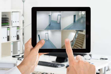 Man Monitoring Camera CCTV Security Videos On Digital Tablet At Office