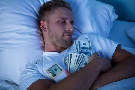 Photo pour Man Sleeping On Bed With Bundle Of Currency Notes - image libre de droit