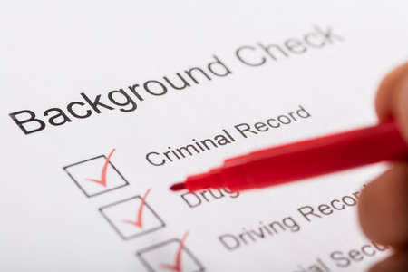 Photo pour Close-up Of Person Hand Ticking Off Checkboxes In Background Check Form - image libre de droit