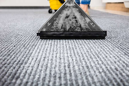Photo for Close-up Of A Cleaning Carpet With Vacuum Cleaner - Royalty Free Image