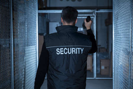 Photo pour Rear View Of A Security Guard Standing In The Warehouse Holding Flashlight - image libre de droit