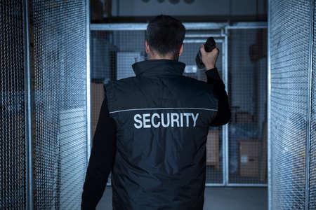 Foto de Rear View Of A Security Guard Standing In The Warehouse Holding Flashlight - Imagen libre de derechos