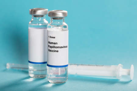 Photo pour Human Papillomavirus Vaccine In Bottles With Syringe Over Turquoise Background - image libre de droit