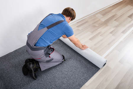 Young Male Handyman Rolling Carpet On Floor At Home