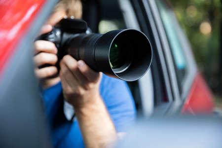 Photo pour Private Detective Sitting Inside Car Photographing With SLR Camera - image libre de droit