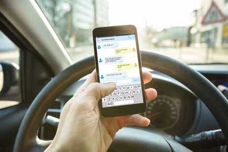 Photo pour Close-up Of A Person Sending A Text Message Using Mobile Phone While Driving A Car - image libre de droit