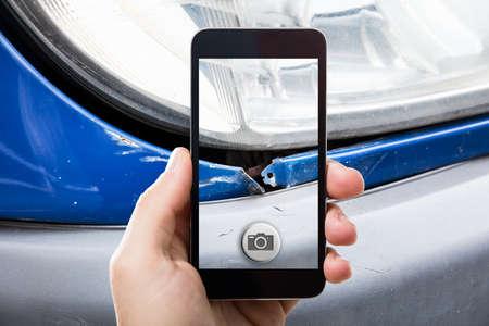 Photo pour Close-up Of A Person Taking Picture Of A Damaged Car On Mobile Phone - image libre de droit