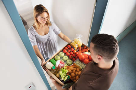Photo for Elevated View Of Smiling Young Woman Accepting Cardboard Box Full Of Groceries From Delivery Man - Royalty Free Image