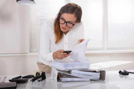 Photo pour Young Businesswoman Taking Photo's Of Document Secretly Kept On Desk In Office - image libre de droit