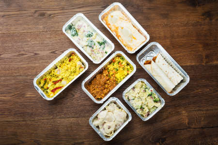 Different Type Of Ready Tasty Meals In Foil Containers On The Table