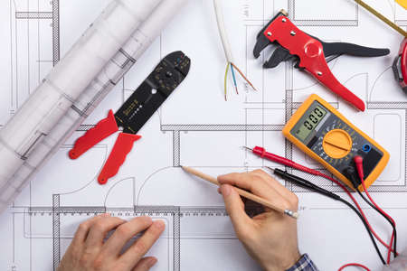 Photo for Elevated View Of An Architect Drawing Plan On Blueprint With Electrical Components - Royalty Free Image