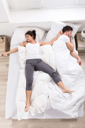 Photo pour Overhead View Of Young Woman Sleeping Beside Her Husband On Bed - image libre de droit