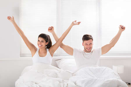 Photo pour Smiling Young Couple With Their Arm Raised Sitting On Bed At Morning - image libre de droit