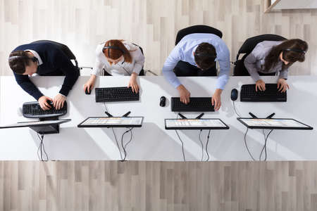 Foto de Elevated View Of Call Center Operator Team With Headset Working In Office - Imagen libre de derechos
