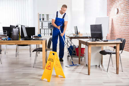 Photo pour Male Janitor Cleaning Floor With Caution Wet Floor Sign In Office - image libre de droit