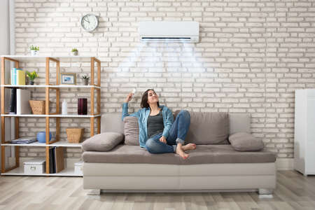 Photo for Happy Young Woman Holding Remote Control Relaxing Under The Air Conditioner - Royalty Free Image