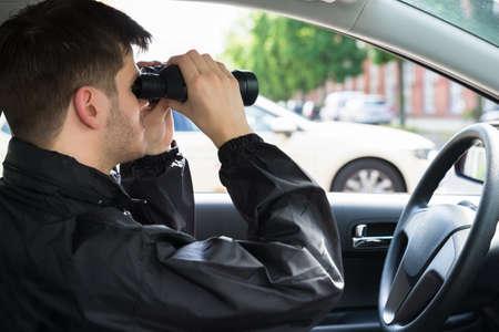 Photo pour Close-up Of A Man Sitting Inside Car Looking Through Binocular - image libre de droit