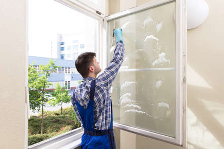 Photo for Rear View Of A Young Male Housekeeper Cleaning Window - Royalty Free Image