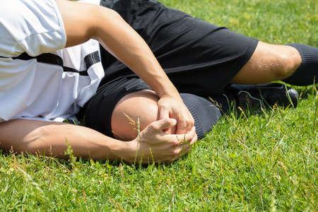 Foto de Close-up Of Male Player Suffering From Knee Injury Lying On Field - Imagen libre de derechos