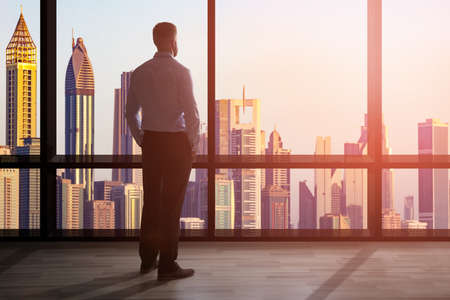 Photo for Businessman Standing At The Large Window Of A High Office Overlooking The Cityscape - Royalty Free Image