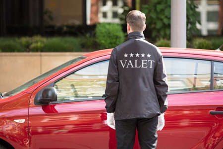 Photo pour Rear View Of A Valet Standing In Front Of Red Car - image libre de droit