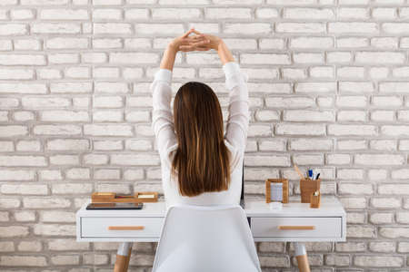 Photo pour Rear View Of A Young Businesswoman Sitting On Chair Stretching Her Arms - image libre de droit