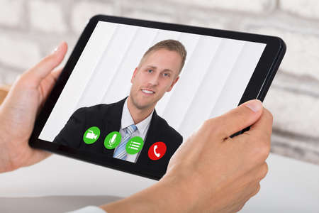 Photo for Businessperson Videoconferencing With Happy Male Colleague On Digital Tablet - Royalty Free Image