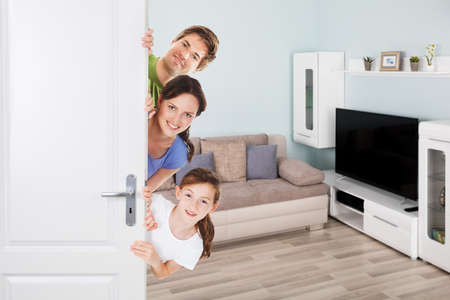 Photo pour Portrait Of Happy Family Peeking From Door In Living Room - image libre de droit