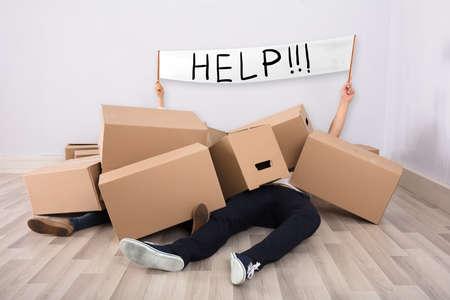 Photo pour Couple Lying Under The Heap Of Cardboard Boxes On Floor Showing White Help Flag - image libre de droit