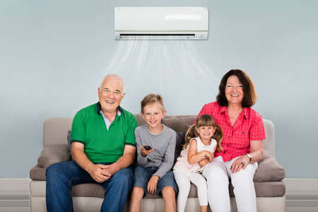 Photo pour Happy Multi Generation Family With Two Kids Watching Television Under Air Conditioning At Home - image libre de droit