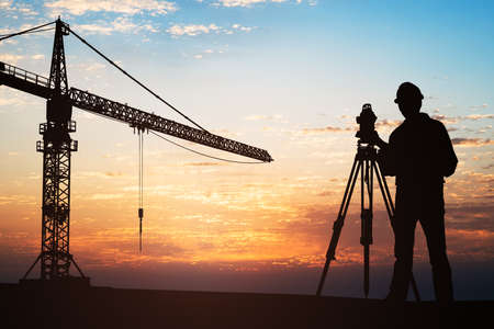 Photo pour Silhouette Of A Surveyor Standing With Equipment Near Crane At Construction Site During Sunset - image libre de droit