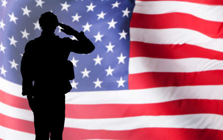 Foto per Silhouette Of A Solider Saluting Against The American Flag - Immagine Royalty Free